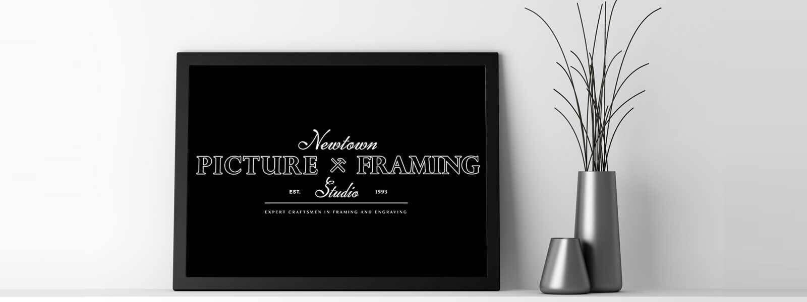 a framed logo of Newtown Picture Framing beside an elegant steel vase